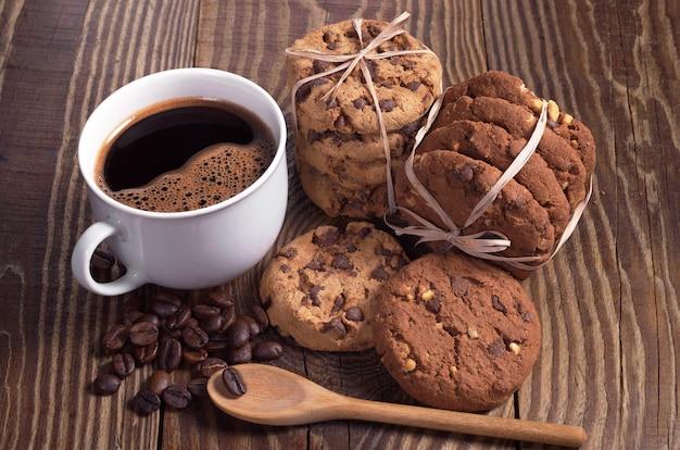 나무 테이블에 리본으로 묶인 뜨거운 커피와 초콜릿 쿠키 한 잔