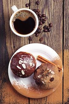Чашка горячего кофе и шоколадный кекс с орехами на деревянном столе