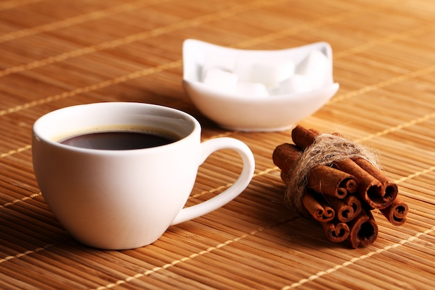 Чашка горячего кофе и палочки корицы