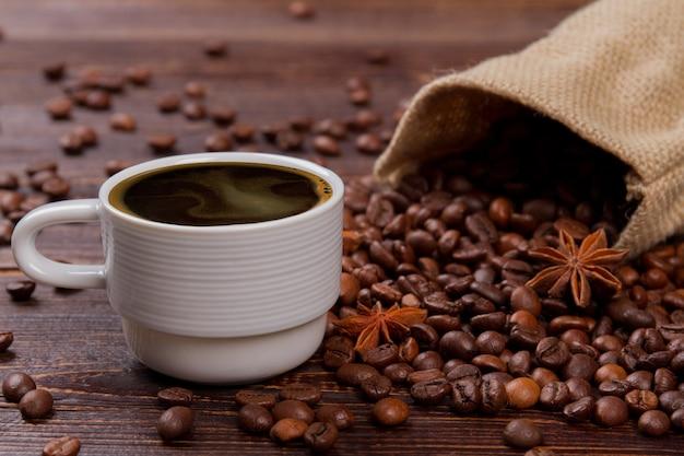 アニスとホット コーヒーとコーヒー豆のカップ