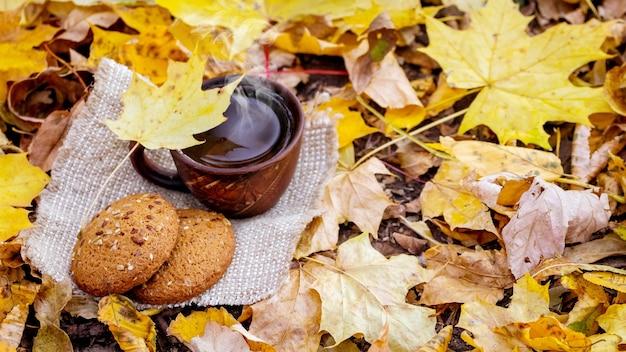 Чашка горячего кофе и печенья в лесу среди желтых листьев