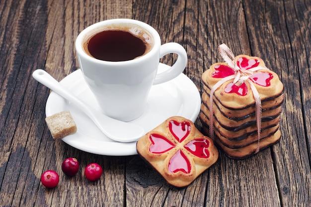 뜨거운 커피 한 잔과 쿠키가 나무 테이블에 리본과 크랜베리를 묶었다