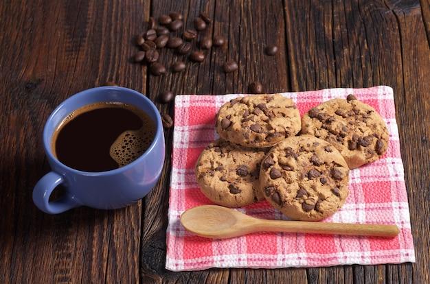 어두운 나무 테이블에서 아침 식사로 따뜻한 커피와 초콜릿 쿠키 한 잔