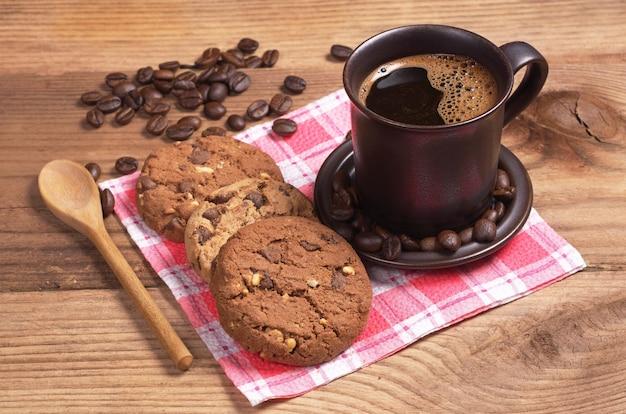 오래된 나무 테이블에서 아침 식사로 따뜻한 커피와 초콜릿 쿠키 한 잔