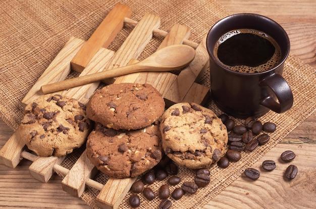 소박한 나무 테이블에서 아침 식사로 따뜻한 커피와 초콜릿 쿠키 한 잔