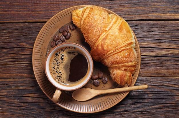 어두운 나무 테이블에 있는 접시에 뜨거운 커피와 크루아상 한 잔, 위쪽 전망