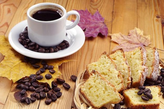 Чашка горячего кофе и кекс на деревянном столе