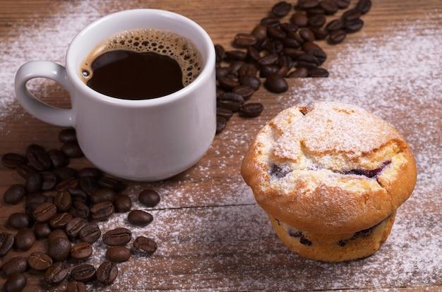나무 배경에 잼을 얹은 뜨거운 커피와 신선한 머핀 한 잔