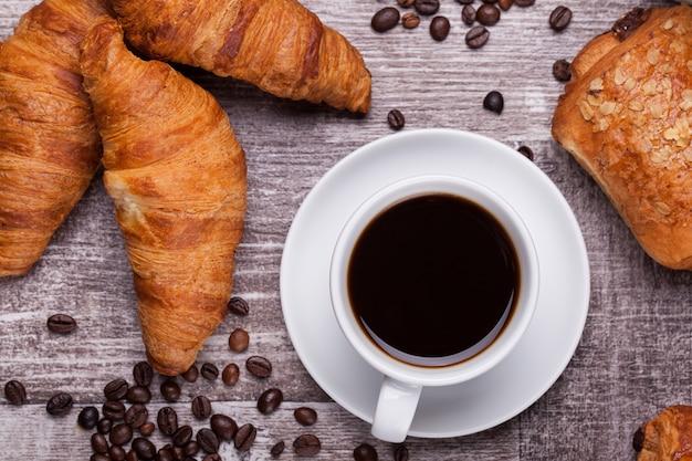 어두운 나무 테이블에 뜨거운 커피와 갓 구운 크루아상 한 잔. 맛있는 크루아상.