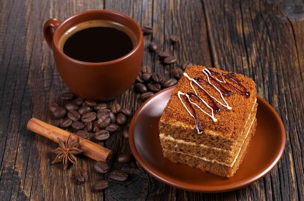 Чашка горячего кофе и медовый торт на темном деревянном столе