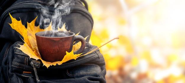 秋の森のバックパックにホットコーヒーとカエデの葉のカップ