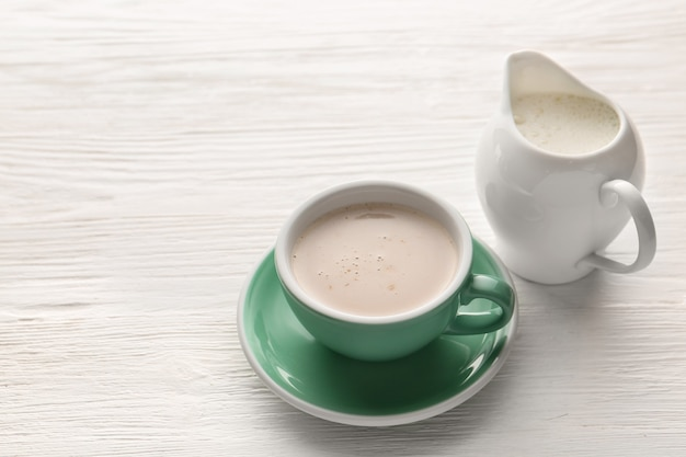 白い木製のテーブルの上のホットコーヒーとミルクのカップ