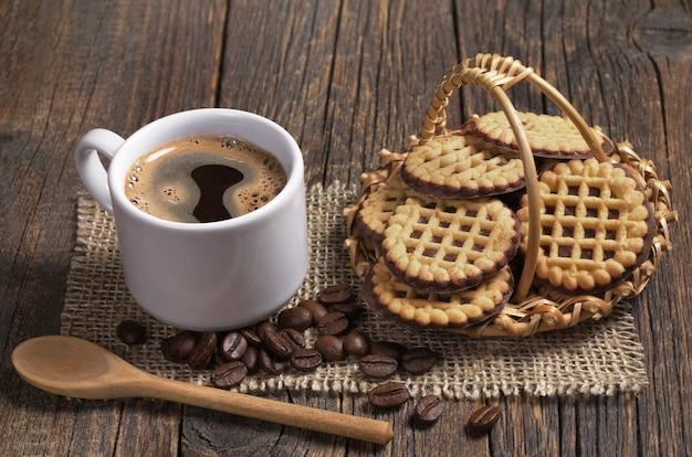 一杯のホットコーヒーとバスケットの丸いクッキー