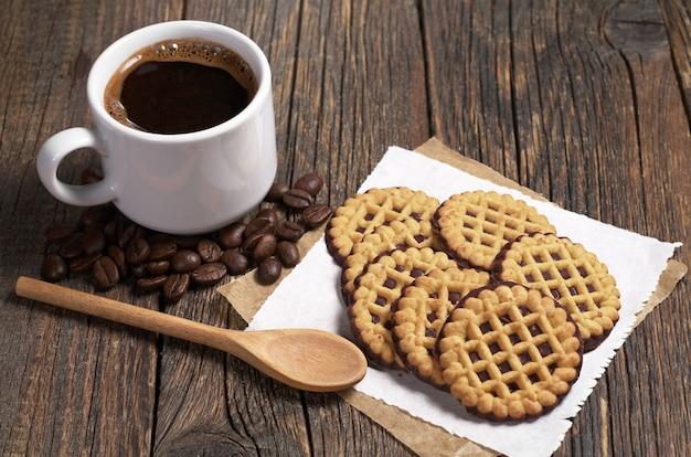 Чашка горячего кофе и круглое печенье с шоколадом