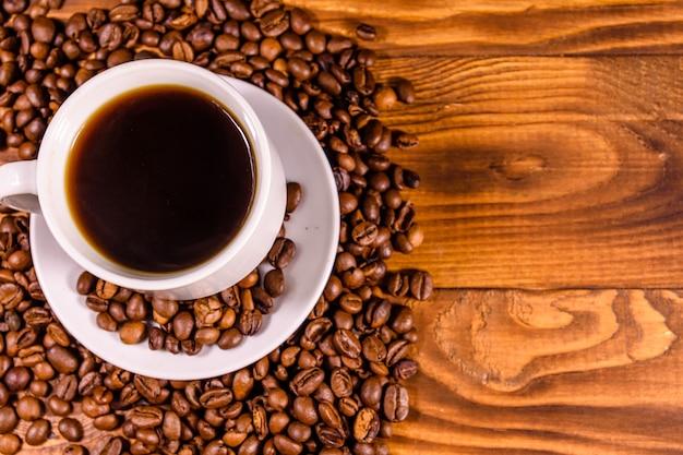 Чашка горячего кофе и разбросанных кофейных зерен на деревенском деревянном столе. вид сверху