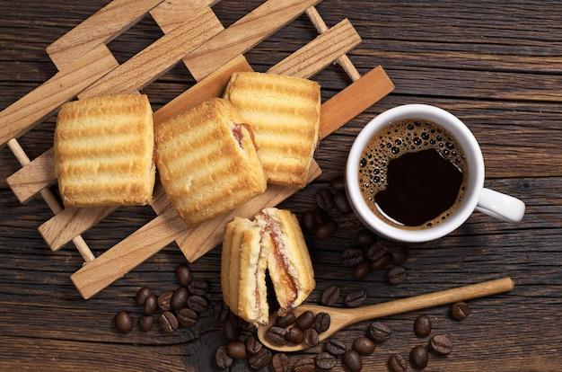 Чашка горячего кофе и песочное печенье с джемом на темном деревянном столе, вид сверху