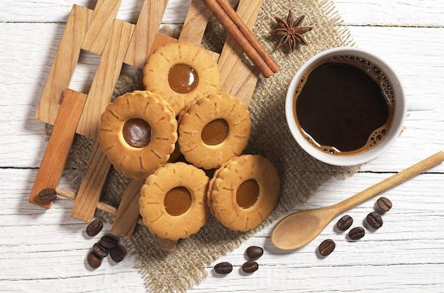 ホットコーヒーとキャラメルと甘いクッキーのカップ