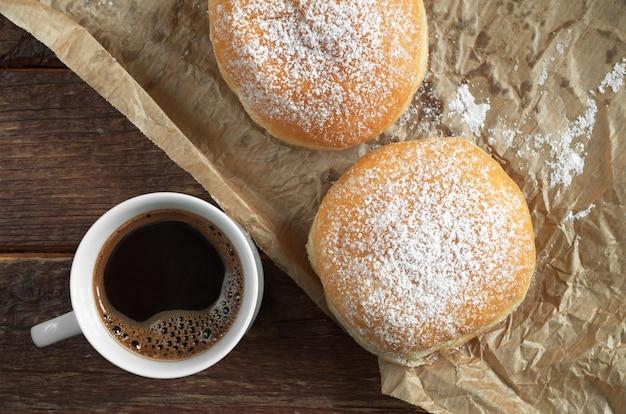구겨진 종이에 가루 설탕을 넣은 뜨거운 커피 한 잔과 도넛 2개, 위쪽