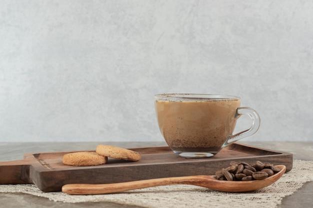 Чашка горячего кофе, печенье на деревянной доске с кофейными зернами