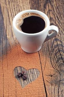 Чашка горячего кофе, кофейных зерен и шоколада в форме сердца