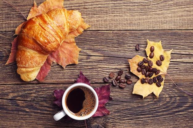 ホットコーヒー、クロワッサン、紅葉のカップ