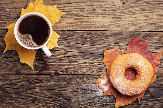 Чашка горячего кофе, пончик и осенние листья