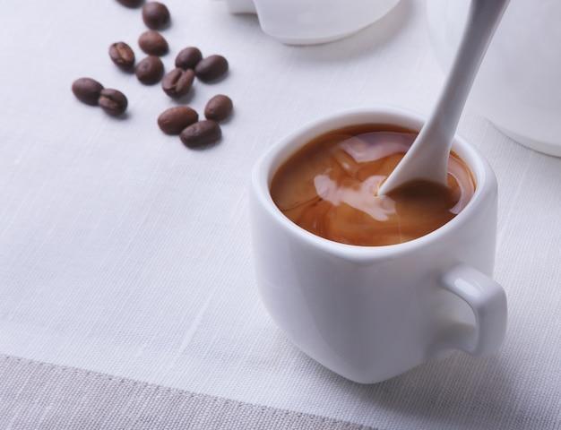 ホットコーヒーエスプレッソ、コーヒー豆、ミルクの水差し、コピースペースの白い背景に砂糖を入れたボウルのカップ。コーヒーのコンセプト。