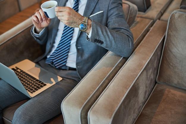 세련된 사업가의 손에 뜨거운 커피 한 잔