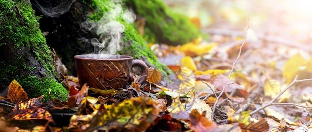 木の下の秋の森でホットコーヒーのカップ。秋の森で休む