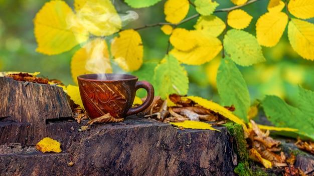 森の中で、色とりどりの葉の間の切り株にあるホット コーヒー。森の中で休む