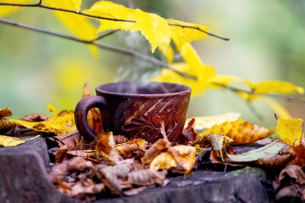 色とりどりの葉の間の切り株の森の中でホットコーヒーのカップ。森の中で休む