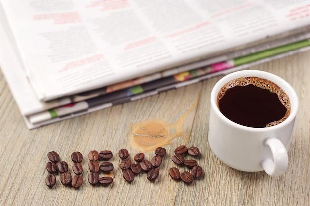 一杯のホットコーヒー、新聞、木製テーブルの単語ニュース