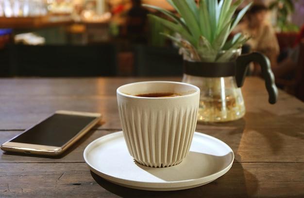 Чашка горячего кофе на деревянном столе с размытым смартфоном и горшечным растением
