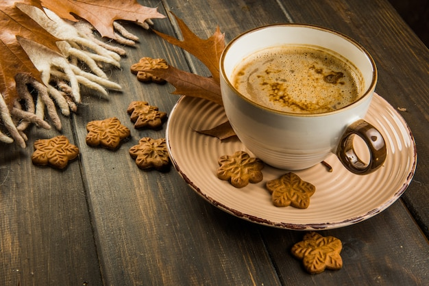 Чашка горячего кофе на рождество и сладкое печенье, плед с коричневыми дубовыми листьями, вид сверху на деревянном фоне