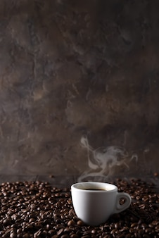 Cup of hot coffee on the background of coffee grains on a dark wooden background
