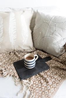 ソファの上のホットコーヒーのカップ