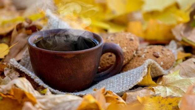 秋の黄色の葉にホットコーヒーまたは紅茶とクッキーのカップ