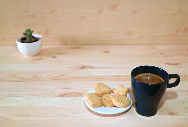 木製のテーブルにビスケットのプレートとホットコーヒーのカップ