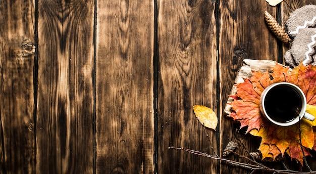 紅葉とホットコーヒーのカップ。木製の背景に。