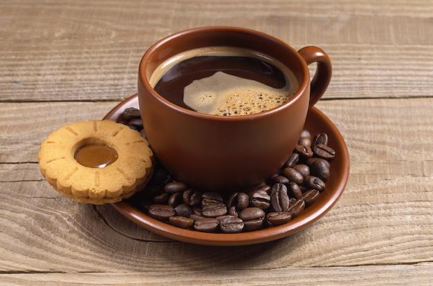 Чашка горячего кофе с печеньем на деревянных фоне