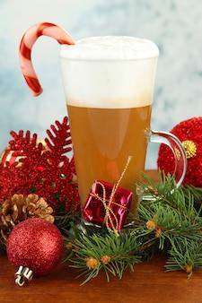 明るい背景のテーブルにクリスマスの装飾とホットコーヒーのカップ