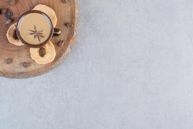 Чашка горячего кофе с палочками корицы на деревянной доске.
