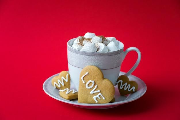 マシュマロと赤い背景の上の愛の言葉とハートビスケットとホットコーヒーのカップ。バレンタインデーのグリーティングカードまたはコーヒーカフェのコンセプト。