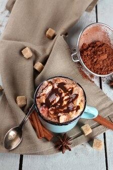Чашка горячего кофе с зефиром на ткани с кусковым сахаром, корицей, звездчатым анисом и красителем какао на стене цветных деревянных досок