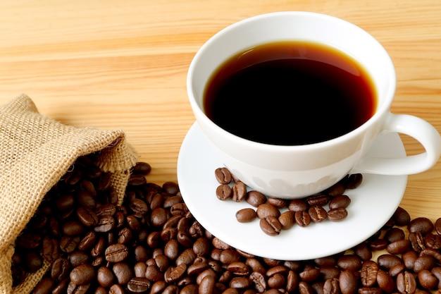 木製のテーブルの黄麻布の袋から散らばっているローストコーヒー豆とホットコーヒーのカップ
