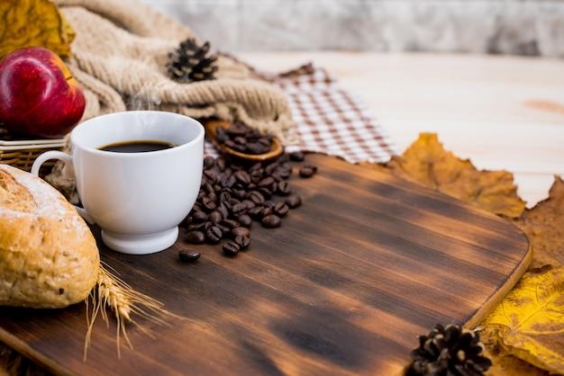 秋の季節の温かい飲み物のためのトーストとホットコーヒーのカップ。秋の収穫の宝庫。木の背景にスペースをコピーします。
