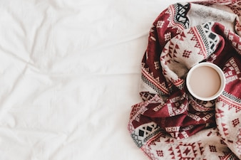 Cup of hot drink in patterned plaid on bedsheet