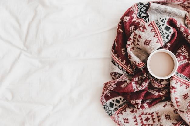 Чашка горячего напитка в узорчатом пледе на простыне