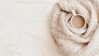 Cup of hot drink in plaid on bedsheet