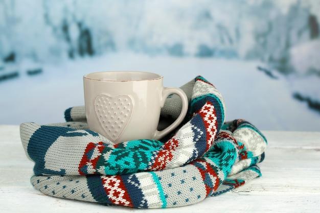 テーブルの上に暖かいスカーフと温かい飲み物のカップ